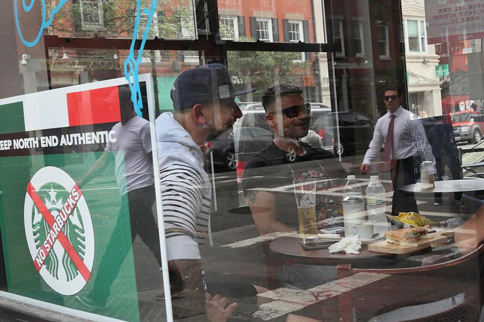 Boston, MA., 06/27/18, In the North End, an anti-Starbucks sign hangs in the window of Caffe dello Sport. Local business owners and customers are speaking out against the addition of a Starbucks at the gateway to the North End on Hanover Street. They argue the store will hurt family-owned coffee houses and diminish the authenticity of the historic neighborhood. Suzanne Kreiter/Globe staff